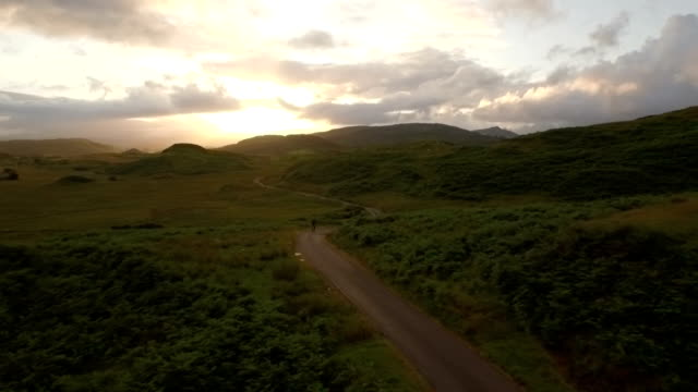 drone shot of a man cyling along a quiet road in scotland during sunrise - twilight stock videos & royalty-free footage
