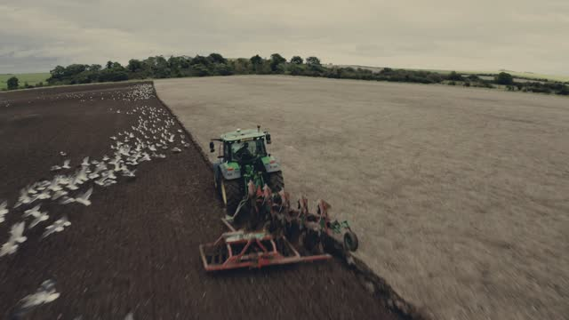 drone shot of a tractor ploughing field in oxfordshire, england, united kingdom, europe - oxfordshire stock videos & royalty-free footage
