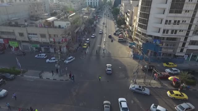 drone shot of a traffic officer directing cars and street traffic in a fourway intersection in gaza palestine - anweisungen geben stock-videos und b-roll-filmmaterial