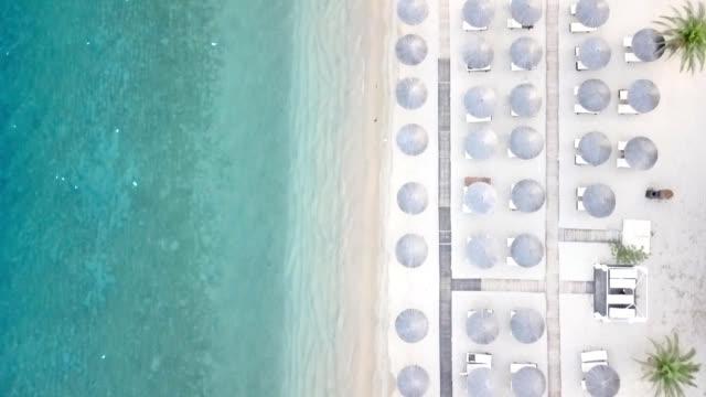 vídeos de stock, filmes e b-roll de tiro do zangão de guarda-chuvas de praia pelo litoral - chapéu de sol