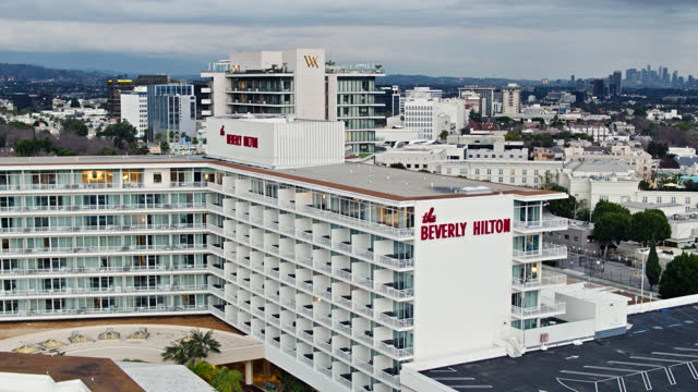 vidéos et rushes de drone shot of beverly hilton hotel and los angeles cityscape - the beverly hilton hotel