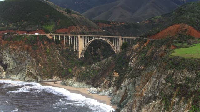 drone shot of big sur flying away from bixby creek bridge - bixby creek bridge stock videos & royalty-free footage