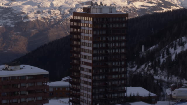 vidéos et rushes de drone tiré des bâtiments sur le flanc de la montagne de la plagne en france - en haut