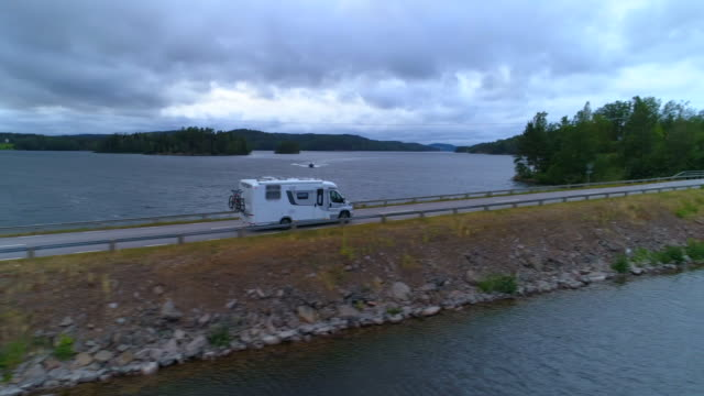 drone shot of camper van on bridge over lake against cloudy sky - asunden, sweden - cumulus stock videos & royalty-free footage