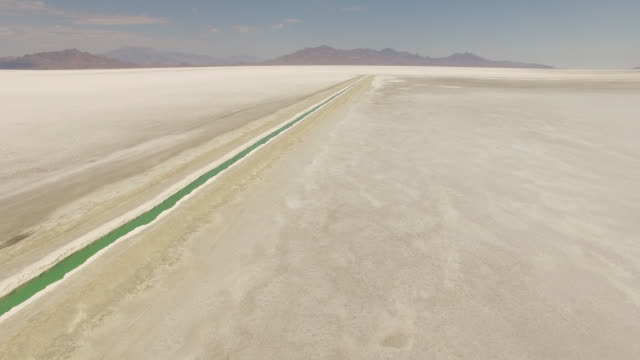 drone shot of canal at bonneville salt flats against mountains - bonneville salt flats stock videos & royalty-free footage