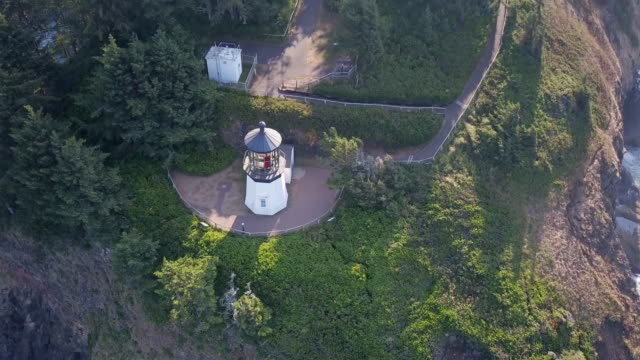 drone shot of cape meares lighthouse, oregon, with dramatic lens flare - oregon coast stock videos & royalty-free footage