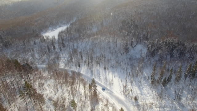 Drone shot of car drifting and speeding on snowbound road