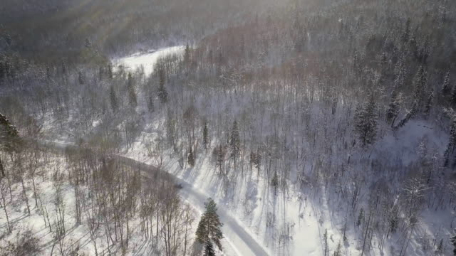 Drone shot of cars racing on snowy road in winter forest