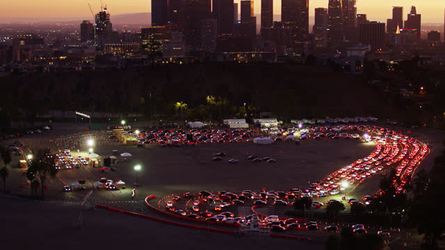 drone shot of cars slowly entering drive-thru covid-19 testing site at dodger stadium with reveal of downtown skyline - sport venue stock videos & royalty-free footage