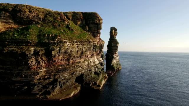drone shot of dramatic sea stacks at duncansby head near john o' groats in scotland - ロックストラータ点の映像素材/bロール