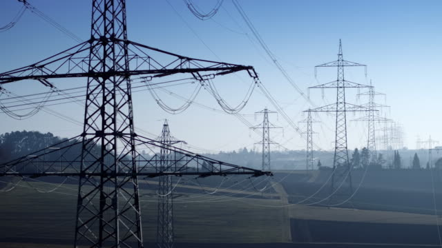 drone shot of electricity pylons in agricultural field against sky, baden-wuerttemberg, germany - power line stock-videos und b-roll-filmmaterial