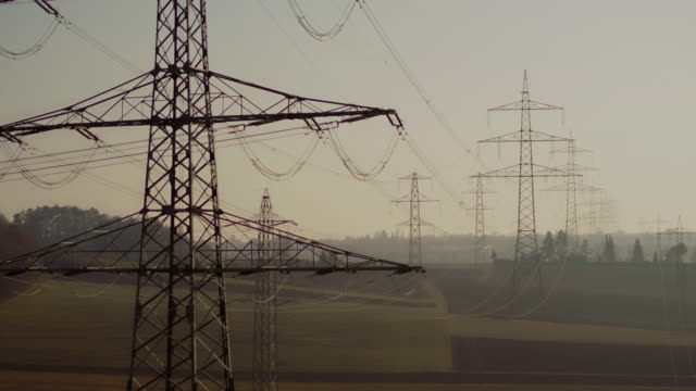 drone shot of electricity pylons in agricultural field, baden-wuerttemberg, germany - electricity pylon stock videos and b-roll footage