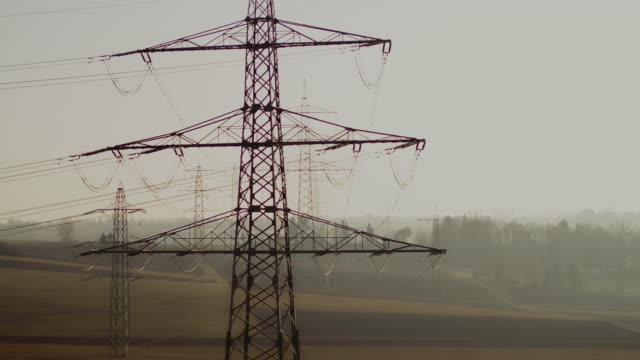 drone shot of electricity pylons in agricultural field - electricity pylon stock videos and b-roll footage