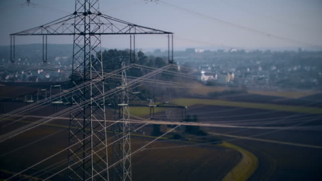 drone shot of electricity pylons in field near town, stuttgart, baden-wuerttemberg, germany - stromleitung stock-videos und b-roll-filmmaterial