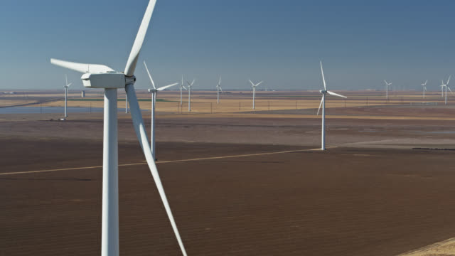 drone shot of enormous turbines at texas panhandle wind farm - windkraft stock-videos und b-roll-filmmaterial
