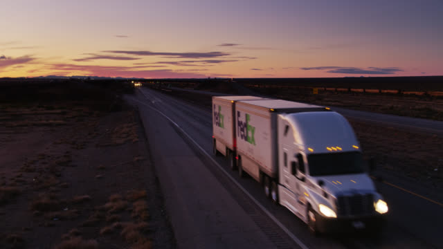 drone shot of fedex truck on interstate at sunset - interstate 10 stock videos & royalty-free footage