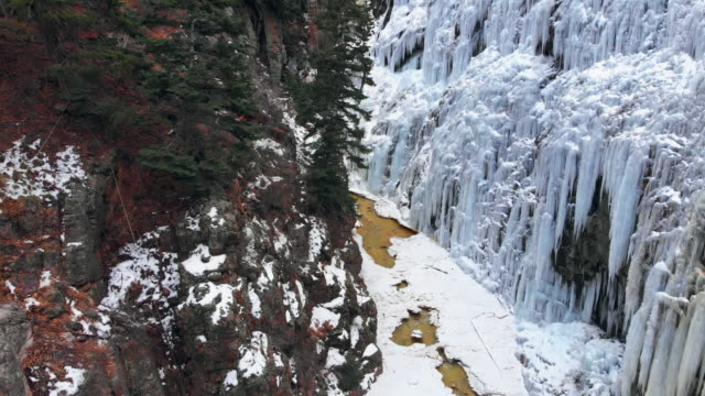 drone shot of flying through a narrow mountain canyon with snow, a stream, and a wall of icicles (ice park) in ouray, colorado - cliff stock videos & royalty-free footage