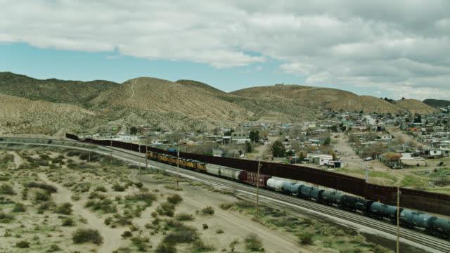 drone shot of freight train pulling oil tank cars alongside us/mexico border wall near el paso - international border barrier stock videos & royalty-free footage