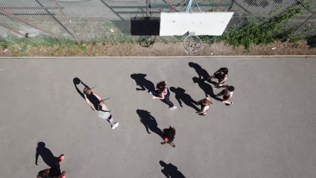 drone shot of friends playing basketball on court - basketball ball stock videos & royalty-free footage