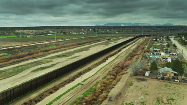 drone shot of houses abutting u.s.-mexico border wall - border stock videos & royalty-free footage