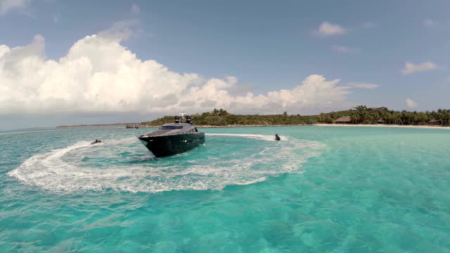 drone shot of jet skis circling luxury yacht in bahamas - segeljacht stock-videos und b-roll-filmmaterial