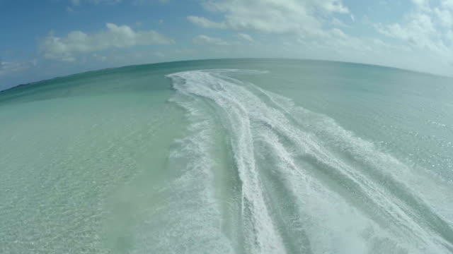 Drone shot of jet skis pulling up on sand island in Bahamas
