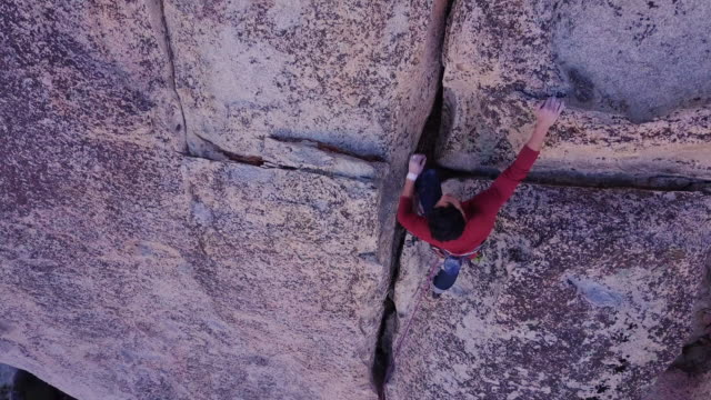 drone shot of lead climber placing anchor - rock climbing stock videos & royalty-free footage