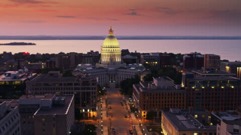 drone shot of madison and the wisconsin state capitol building backed by lake mendota at dusk - state capitol building stock videos & royalty-free footage