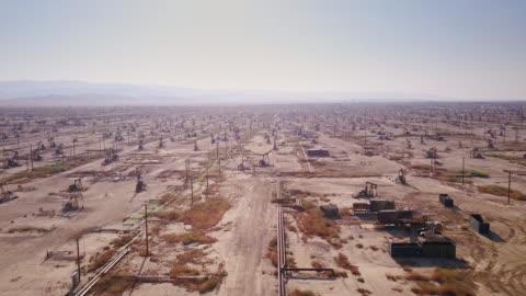 drone shot of massive desert oil field - oil industry stock videos & royalty-free footage