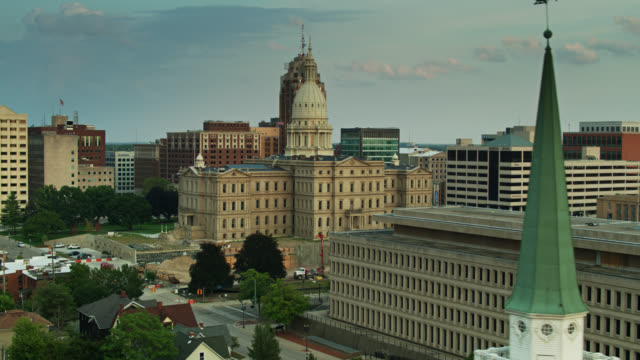 drone shot of michigan state capitol past van wagoner building and church steeple - lansing stock videos & royalty-free footage