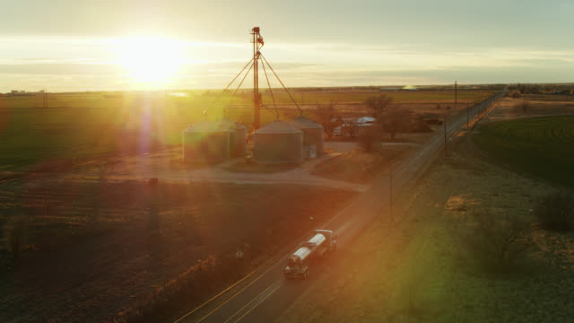 drone shot of milk tanker approaching dairy farm with dramatic lens flare - 30 seconds or greater stock videos & royalty-free footage