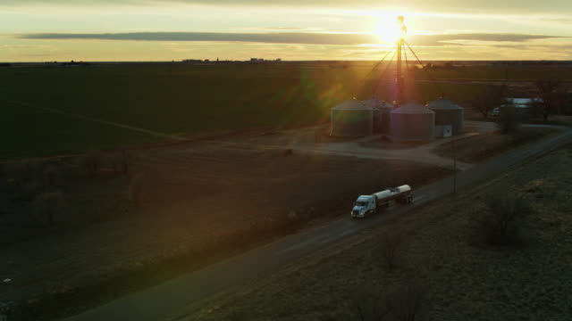 drone shot of milk tanker pulling away from dairy farm past silos - new mexico stock videos & royalty-free footage