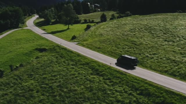 drone shot of mini van on road in remote location - van vehicle stock videos & royalty-free footage