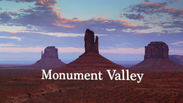 "drone shot of  mitten buttes with floating text: ""monument valley"" - navajo reservation stock videos and b-roll footage"