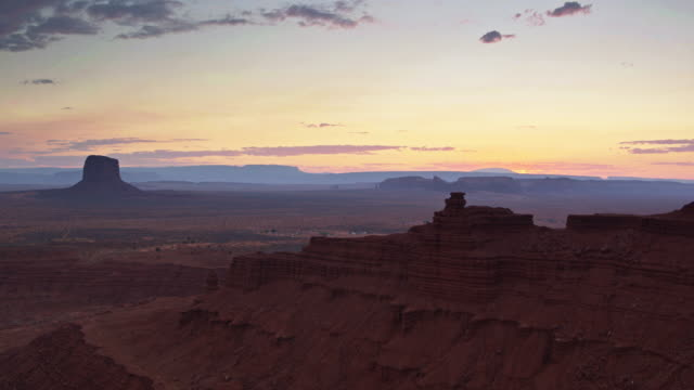 drone shot of monument valley and surrounding desert at dusk - navajo reservation stock videos and b-roll footage