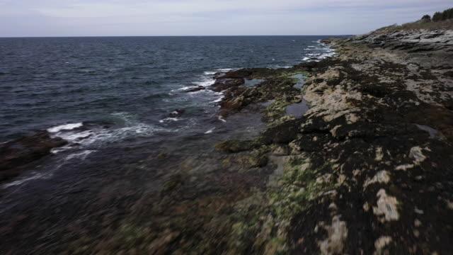 drone shot of ocean waves crashing on the rocky coastline - north atlantic ocean stock videos & royalty-free footage