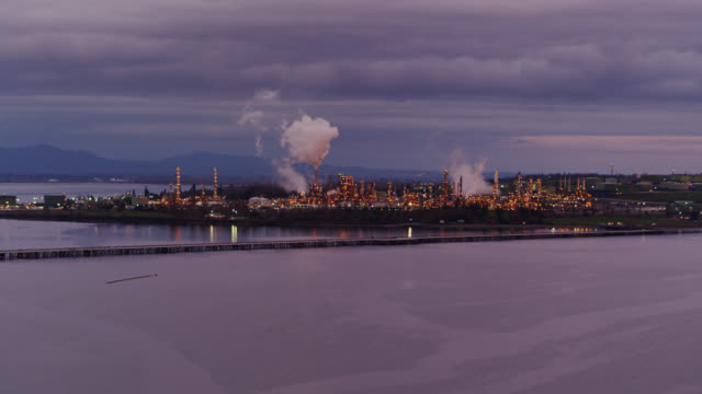 drone shot of oil refinery on fidalgo bay at twilight - anacortes stock videos & royalty-free footage