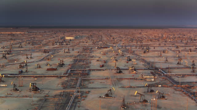 drone shot of oil wells in kern county with distant farmland - industria petrolifera video stock e b–roll