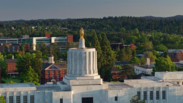 vídeos de stock e filmes b-roll de drone shot of oregon state capitol building with gold pioneer statue shining in evening sunlight - oregon estado dos eua