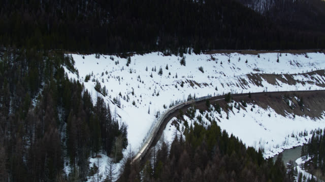 drone shot of passenger train in snowy landscape in montana - glacier national park us stock videos and b-roll footage
