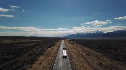 vidéos et rushes de drone shot of paved highway with 18 wheel tractor trailer on sagebrush covered prairie with snow covered mountains in background. - ligne d'horizon au dessus de la terre
