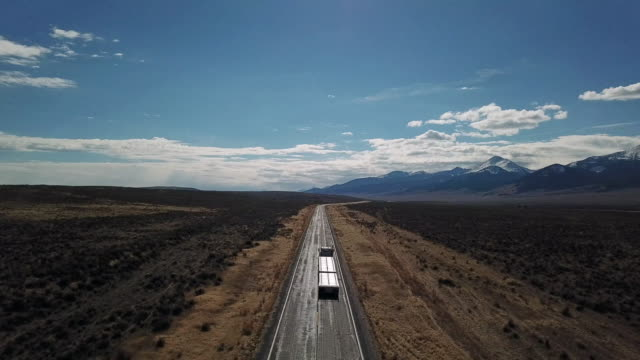 drone shot of paved highway with 18 wheel tractor trailer on sagebrush covered prairie with snow covered mountains in background. - vanishing point stock videos & royalty-free footage