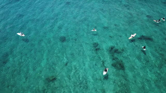 drone shot of people sitting on surfboards in sea during summer - sitting stock videos & royalty-free footage