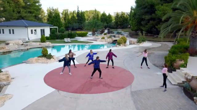 太極拳を練習する若い女性とリゾートでプールのドローンショット - アニメーター点の映像素材/bロール