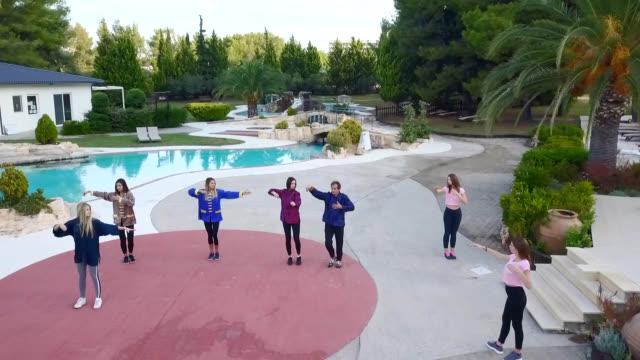 太極拳をしている若い女性とリゾートプールのドローンショット - アニメーター点の映像素材/bロール