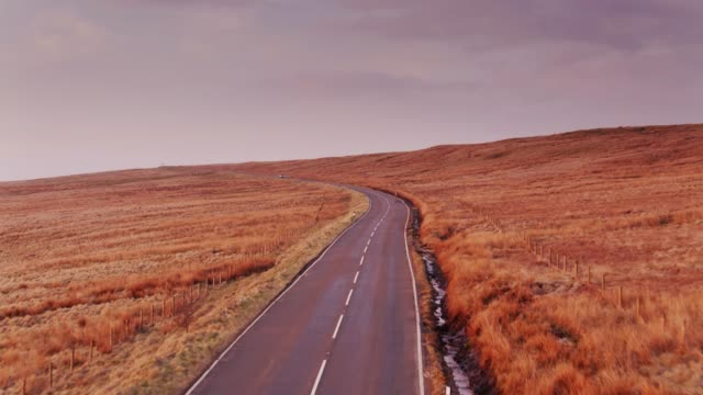 drone shot of road across moorland - pennines stock videos and b-roll footage