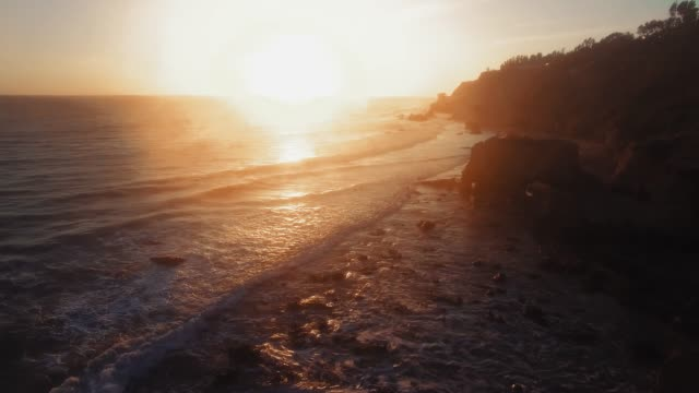 drone shot of setting sun and wavy ocean surface in twilight at el matador beach, malibu, califronia, usa - malibu stock videos & royalty-free footage