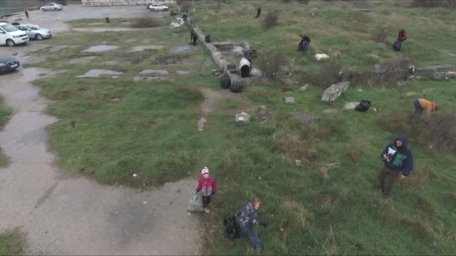 drone shot of several volunteers working together to clean up trash from a grassy hilly area in sevastopol crimea - sevastopol crimea stock videos and b-roll footage