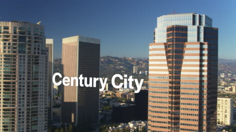 """drone shot of sun shining on skyscrapers with floating text: """"century city"""" - century city stock videos & royalty-free footage"""