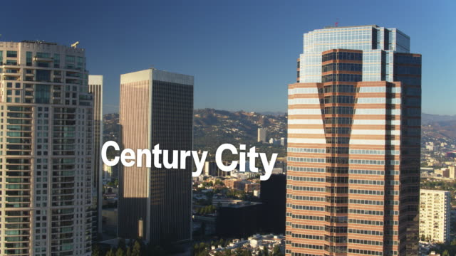 "drone shot of sun shining on skyscrapers with floating text: ""century city"" - century city stock videos & royalty-free footage"